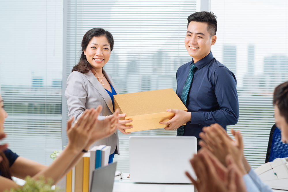 Male and female good employees being praised by their colleagues for their hard work